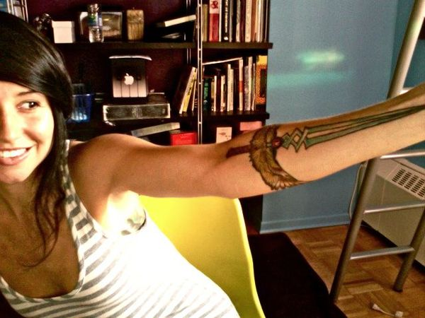 the Twinblade of the Phoenix from World of Warcraft on her left arm