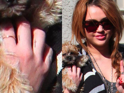 Tattoos On Side Of Fingers. Miley Cyrus finger cross