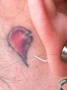 Ash Costello broken heart behind ear tattoo